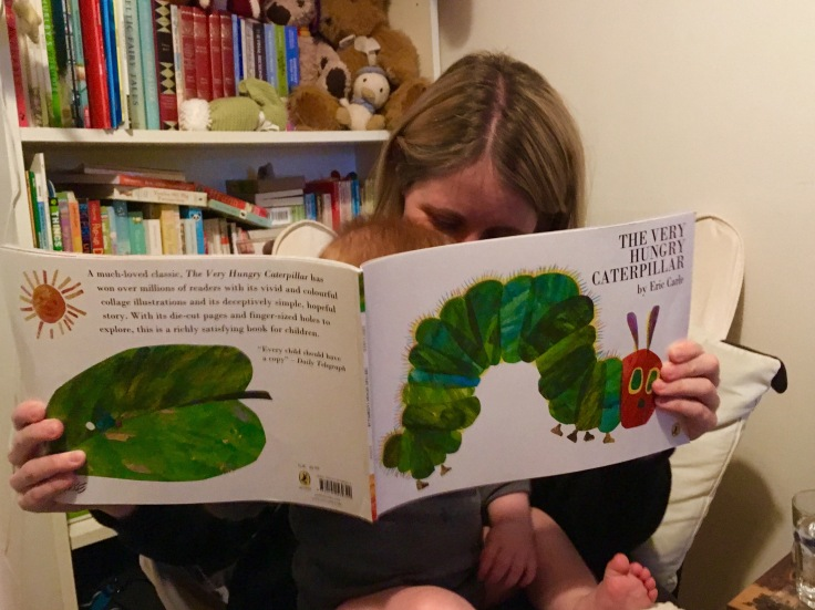 Mum and baby reading The Very Hungry Caterpillar by Eric Carle