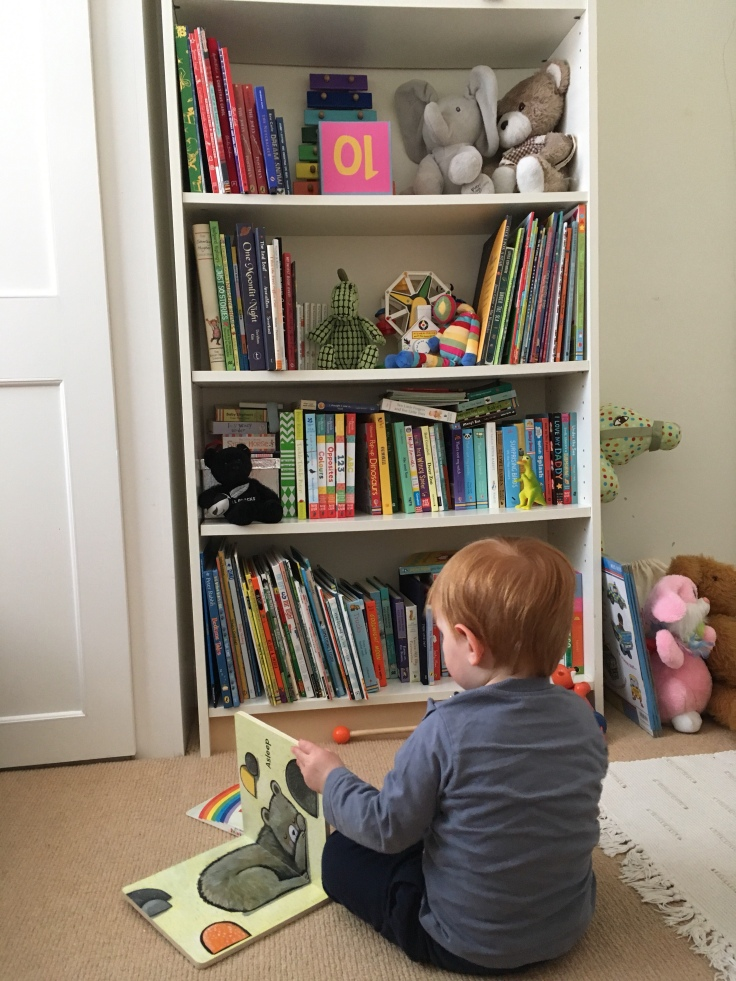 Toddler looking at books beside bookcase