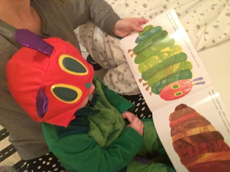 Child reading The Very Hungry Caterpillar by Eric Carle