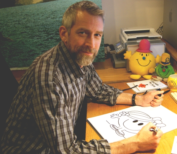 Author Adam Hargreaves sat at his desk drawing a Little Miss character