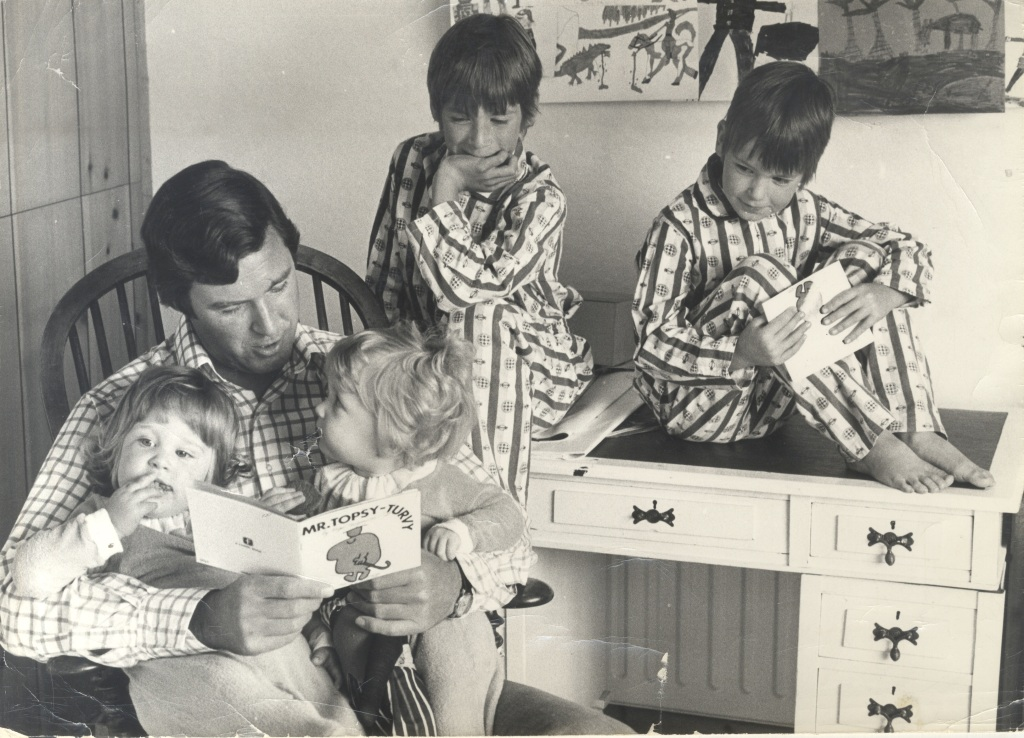 Black and white photo of author Roger Hargreaves reading book Mr. Topsy-Turvy to his four children